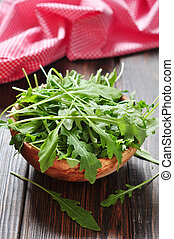 Fresh arugula leaves in wooden bowl on a wooden background