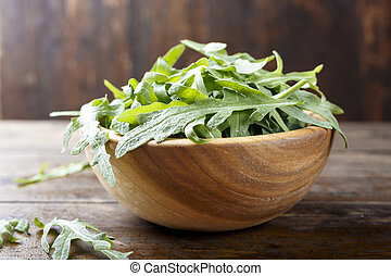 Fresh arugula leaves, rucola, fresh rucola  in a plate, space for text.