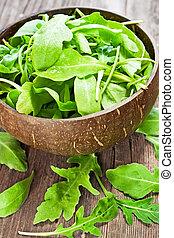 fresh arugula salad on wooden table