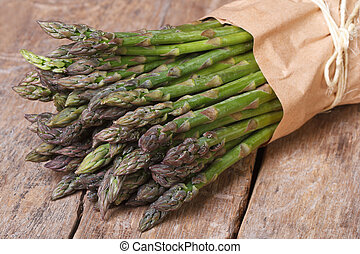 fresh asparagus in a paper bag on wooden table
