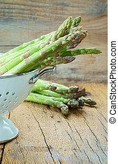 Fresh asparagus in white colander