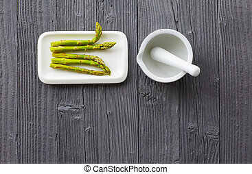 Fresh asparagus served on white plate with mortar on rustic wooden table background, top view.