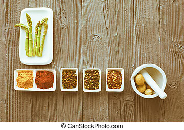 Fresh asparagus served on white plate with rustic wooden table background, top view.