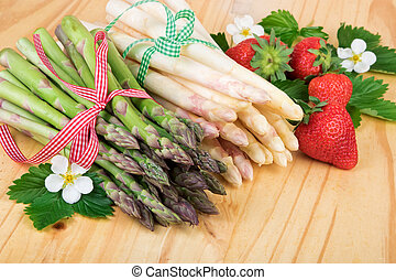 Fresh asparagus with strawberries on wood. Vegan food, vegetarian and healthy cooking concept.