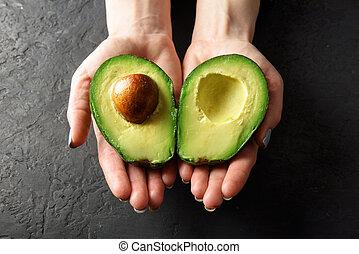 Fresh avocado fruit in girl hands