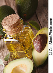 fresh avocado oil in a glass bottle on a table macro, vertical