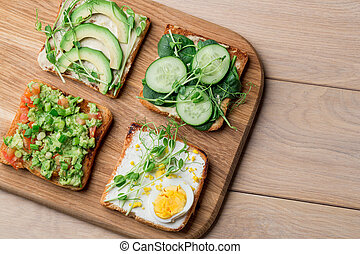 Fresh avocado toasts with different toppings. Healthy vegetarian breakfast with rye whole grain sandwiches