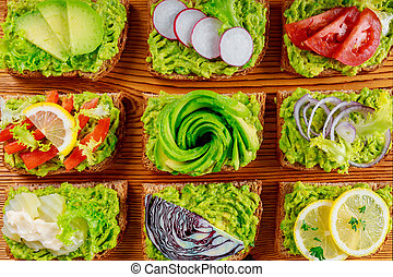 Fresh avocado toasts with different toppings, healthy vegetarian breakfast with wholegrain sandwiches