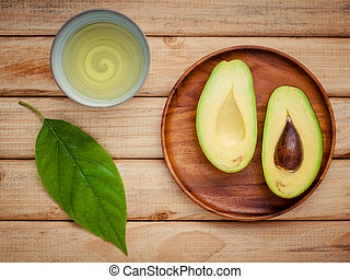 Fresh avocado with avocado leaves and oil on wooden background. Organic avocado healthy food concept.