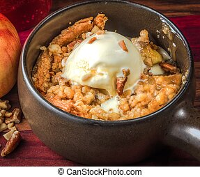 Freshly baked apple crisp a la mode with a walnut topping. A delicious seasonal dessert.