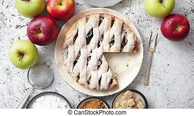 Fresh baked apple pie with cutted slice on small plate. With...