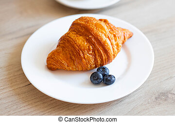 Fresh baked croissant, cup of coffee on the kitchen table. Breakfast concept