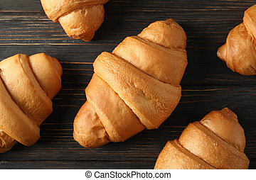 Fresh baked croissants on wooden background, top view