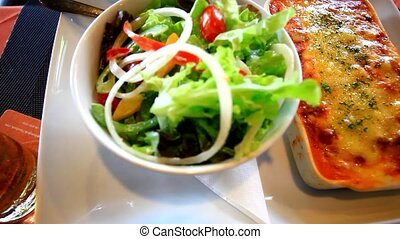 Fresh baked lasagna with vegetable salad. Close up