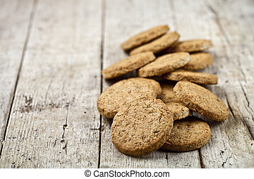 Fresh baked oat cookies heap on rustic wooden table background.