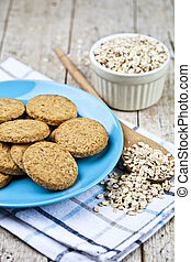 Fresh baked oat cookies on blue ceramic plate on linen napkin and oak flakes on rustic wooden table.