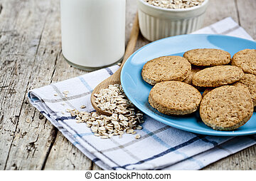 Fresh baked oat cookies on blue ceramic plate on linen napkin, bottle of milk and oak flakes on rustic wooden table.