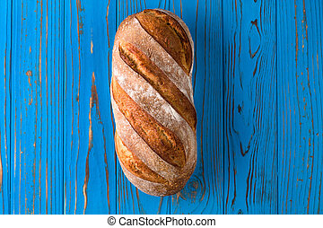 Fresh baked rye bread on a blue wooden background
