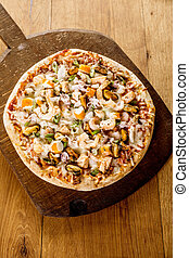 Fresh Baked Seafood Pizza on Wooden Cutting Board