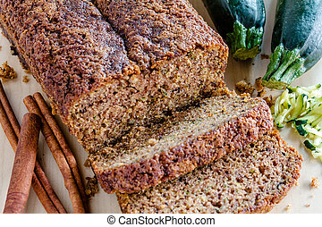 Loaf of homemade zucchini bread sitting on counter with fresh zucchini squash, shreds and cinnamon sticks