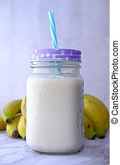 Fresh banana shake on table, close up.