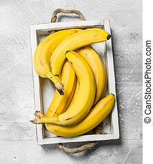 Fresh bananas in a wooden box.