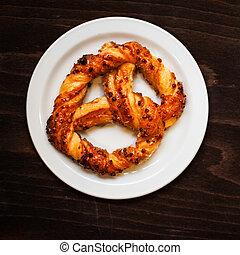 Fresh Bavarian pretzel on dark background with flour. Sweet...