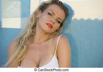 fresh, beautiful blonde woman in white shirt posing on a terrace set beside the sea in summer, Spain
