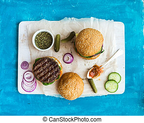 Fresh beef burger with cheese, vegetables, spicy tomato sauce on paper and white serving board, blue wooden background.