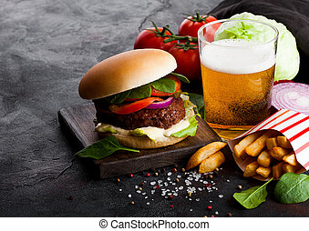 Fresh beef burger with sauce and vegetables and glass of lager craft beer with potato chips fries on stone kitchen table background.
