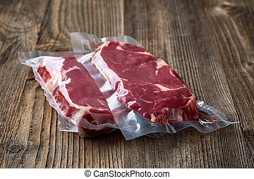 Fresh beef steak for sous vide cooking on wooden table