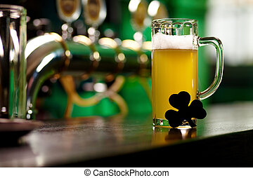 Fresh beer - Image of glass of beer with shamrock leaf on...