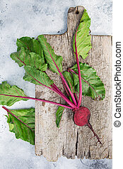 Fresh beetroot with leaves on a wooden board. Healthy food. ...