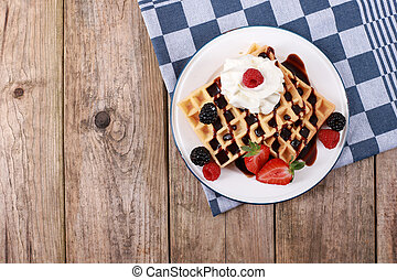 fresh belgian waffles topped with chocolate sauce, strawberries, fruits and berries and whipped cream on rustic wooden table