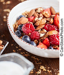 Fresh berries, almonds, oatmeal and granola in a plate with milk on a wooden background. Healthy food