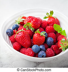 Fresh berries, blueberry, strawberry, raspberry with mint leaves in a white ceramic bowl on a gray stone background