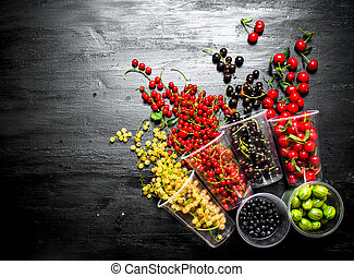 Fresh berries in glasses. On black wooden background.