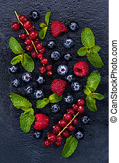 Fresh berries of red currant, raspberry and blueberry and mint leaves