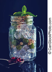 Fresh berries with ice in mason jar on dark background