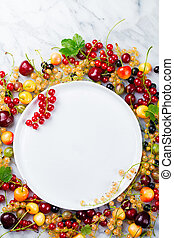 Fresh berries with white plate Copy space Top view