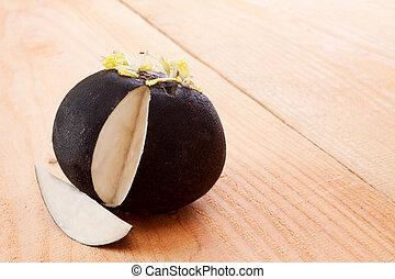 Fresh black radish isolated on wooden background.