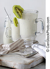 Fresh blended kiwi protein smoothie with yogurt or milk in glass jar, healthy eating