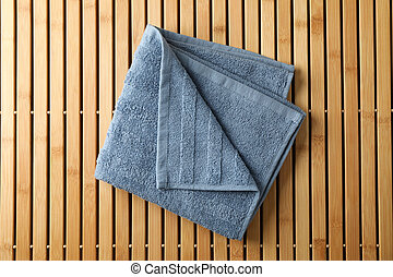 Fresh blue towel on bamboo background, top view