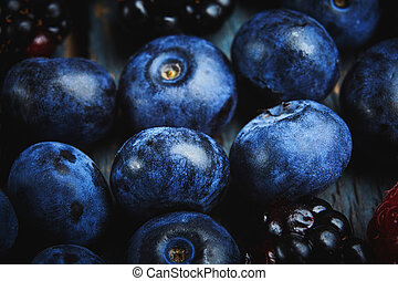 Summer food background. Close up fresh blueberries and blackberries on a dark wooden background