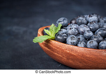 Fresh blueberries with a leaf of mint in the heart-shaped bowl