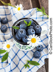 Fresh blueberry in the mug on wooden table