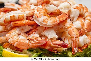 A platter of fresh boiled shrimp on a bed of lettuce and a lemon slice
