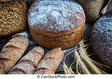 fresh bread, buns and wheat on the wooden background