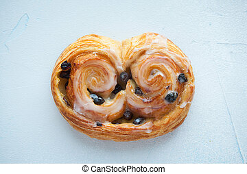 Fresh bread roll with raisins and icing on a blue background. Top view