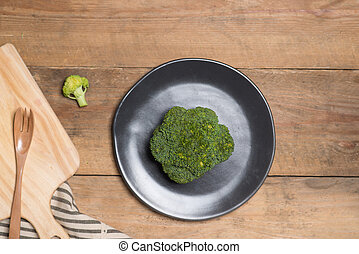 Fresh broccoli in dish on a wooden background